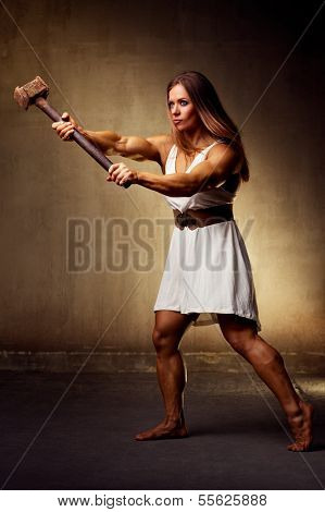 Young woman bodybuilder with hammer.