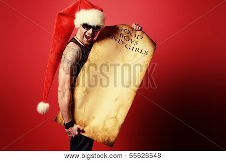Handsome brutal man in Christmas hat holding a list of good boys and girls. Over red background.