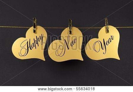Happy New Year Message Greeting Text On Gold Hearts Hanging From Pegs On A Line Against A Black Back