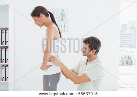 Side view of a male physiotherapist examining woman's back in the medical office