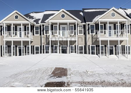 New townhouses under a layer of freshly fallen snow.