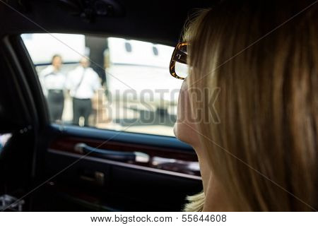 Closeup of elegant woman in limousine at airport terminal