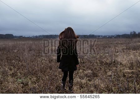 Woman in black coat standing in cold autumn field