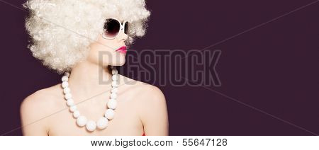 Beautiful sexy woman in a blond afro wig and large trendy sunglasses in profile over a black background with copyspace