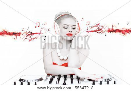 Creative toned portrait of a beautiful disc jockey mixing music wearing headphones with red streaming music