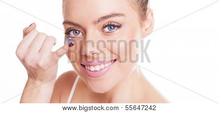 Beautiful woman with a lovely wide smile inserting a contact lens in her eye with her finger, close up studio shot over white