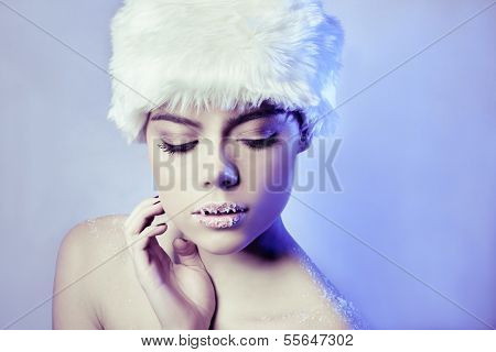 Beautiful seductive winter woman with bare shoulders wearing a white furry hat looking with downcast eyes and frosted lips on a cool blue background