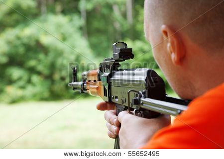 Man Shooting An Automatic Rifle For Strikeball. Focus On The Rifle Sights.