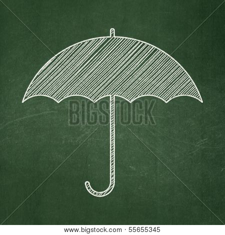 Protection concept: Umbrella on chalkboard background