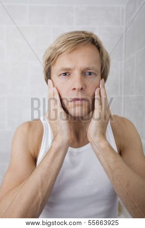 Portrait of man applying aftershave moisturizer in bathroom