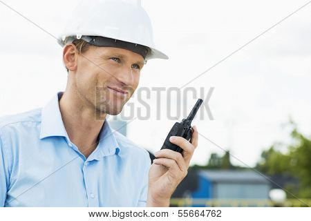 Smiling architect holding two way radio at construction site