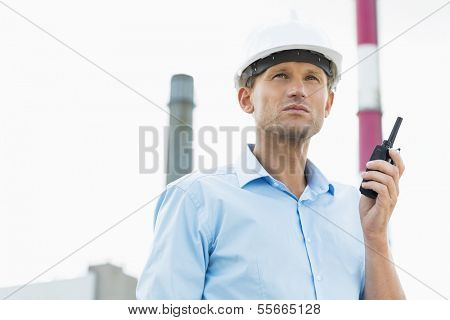 Male architect holding two way radio at site
