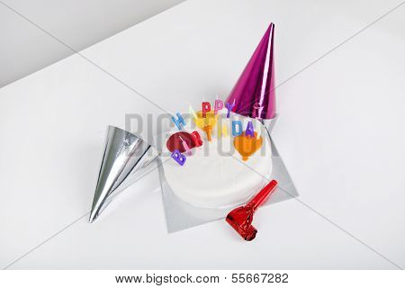Birthday cake with party hats and noisemaker on table