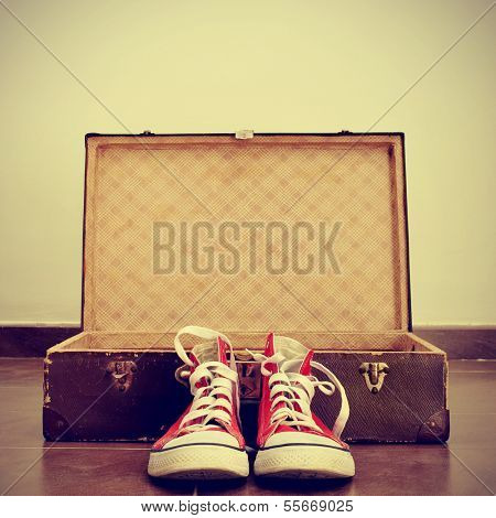 a pair of red sneakers in front of an open old brown suitcase with a retro effect