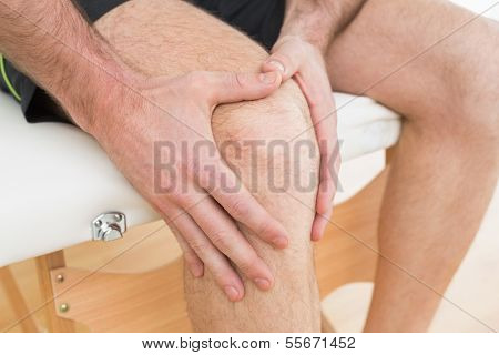 Close-up mid section of a young man with his hands on a painful knee while sitting on examination table