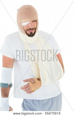 Young man with head tied up in bandage and broken hand over  white background