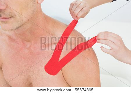 Close-up of a physiotherapist putting on red kinesio tape on patient's shoulder in the medical office