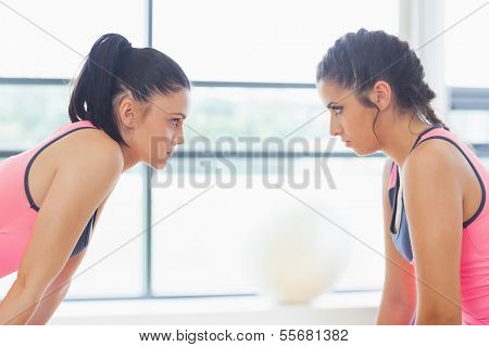 Close-up side view of two angry young women staring at each other at a bright gym