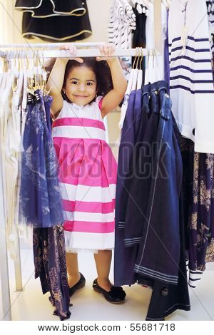 Pretty little girl in dress stands near clothes hangers and smiles in children clothing shop.