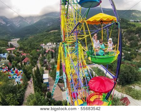 Family of three having fun on the ferris wheel against the mountains and sky with clouds, view from unmanned quadrocopter.