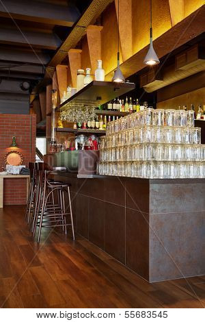 Counter with many empty beer mugs, beverages in bottles, three tall wooden stools in cafe