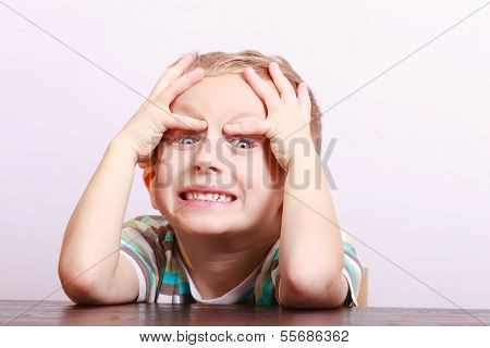 Portrait Of Surprised Angry Emotional Blond Boy Child Kid At The Table