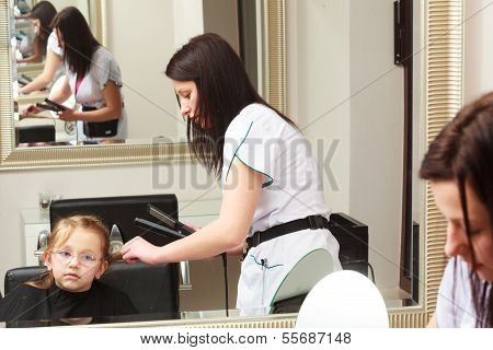 Hairdresser Straightening Hair Little Girl Child In Hairdressing Beauty Salon