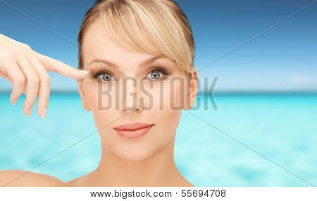 health, spa, beauty and vacation concept - face of beautiful woman touching her eye area
