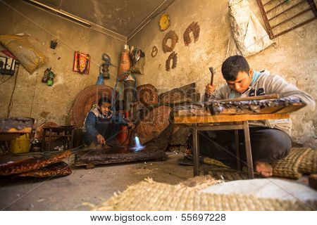 BHAKTAPUR, NEPAL - DEC 5: Unidentified Nepalese tinman working in the his workshop, Dec 5, 2013 in Bhaktapur, Nepal. 100 cultural groups have created an image Bhaktapur as Capital of Nepal Arts.