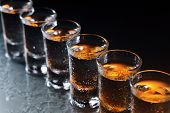 stock photo of shot glasses  - Glasses with an alcoholic drink on a damp glass table