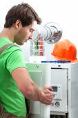 stock photo of boiler  - Handyman repairing boiler in a boiler room - JPG
