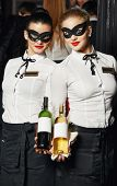 Waitress girl in mask with bottles of wine at restaurant or cafe
