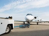 stock photo of cabin crew  - Private business jet being towed by ground crew - JPG