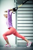 stock photo of suspension  - Young woman streching muscles functional training - JPG