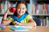 image of schoolgirl  - Portrait of happy schoolgirl with big red apple looking at camera in library - JPG