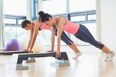 foto of step aerobics  - Side view of two fit women performing step aerobics exercise in gym - JPG