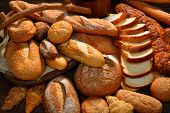 stock photo of wooden basket  - Variety of bread on old wooden background - JPG
