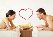 spa, beauty, love and happiness concept - smiling couple with candles in spa salon drinking champagn