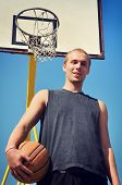 Basketball Player Posing And Smiling Under The Backboard