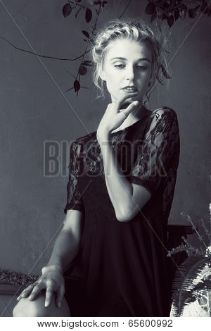 Beautiful blond woman with braid hairstyle and natural makeup. Wearing ping bohemian sequin and feather dress. Against blue grunge background