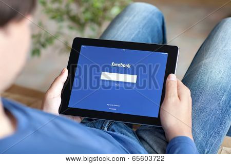 Man Sitting On The Sofa And Holding Ipad With App Facebook On The Screen