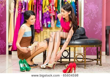 Asian young sales lady offering shoes to woman in fashion store