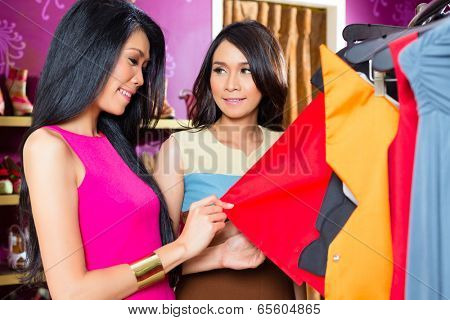 Asian young women choosing garment in fashion store