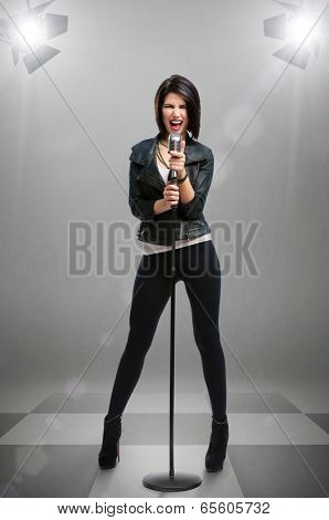 Full-length portrait of rock singer wearing leather jacket and keeping static mic under projectors, isolated on grey. Concept of rock music and rave