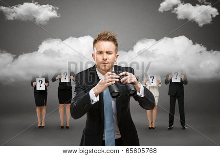 Businessman wearing suit with blue tie and binocular stands against stormy sky and people with question marks over clouds