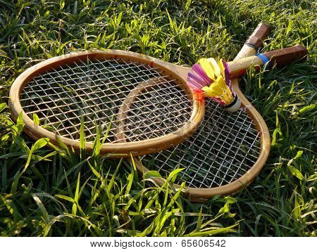 badminton rackets and shuttlecock in the grass