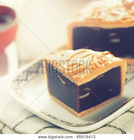 Traditional red beans paste mooncakes on white plate with teacup. Chinese mid autumn festival foods.