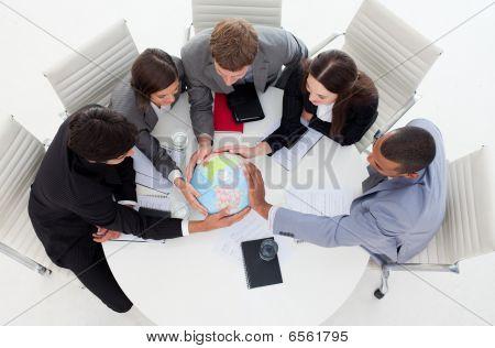 Internatonal Business Team einen terrestrischen Globus Holding