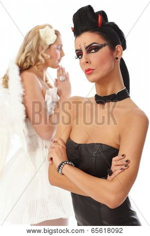 Evil woman looking wicked, angel praying at background.