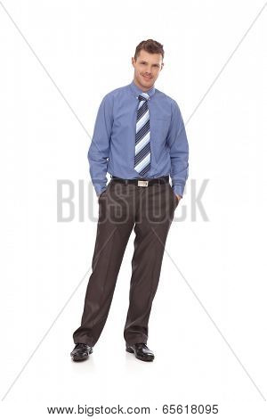 Confident young businessman standing with hands in pockets, smiling. Full-length.